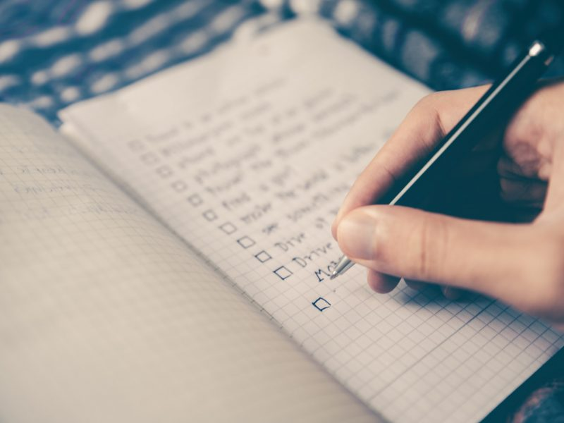 person writing bucket list on notepad